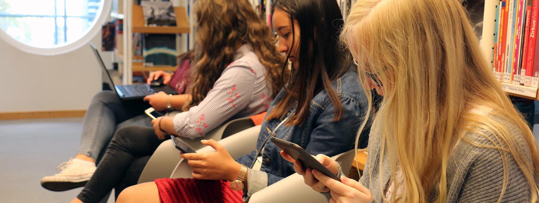 Junge Frauen lesen die Stadtnachrichten auf ihren mobilen Endgeräten