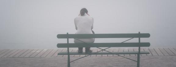 Frau sitzt. mit dem Rücken zum Betrachter, auf Parkbank und schaut in Nebel