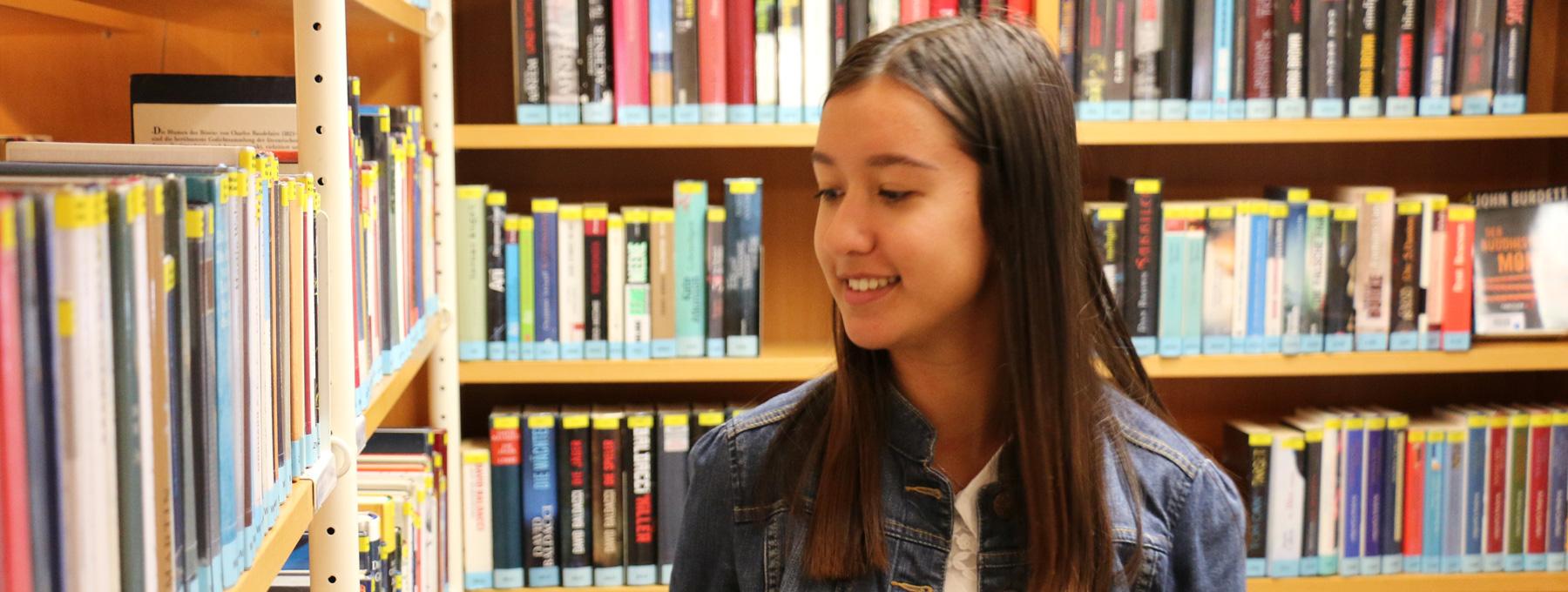 Junge Frau vor Bücherregalen in der Stadtbücherei