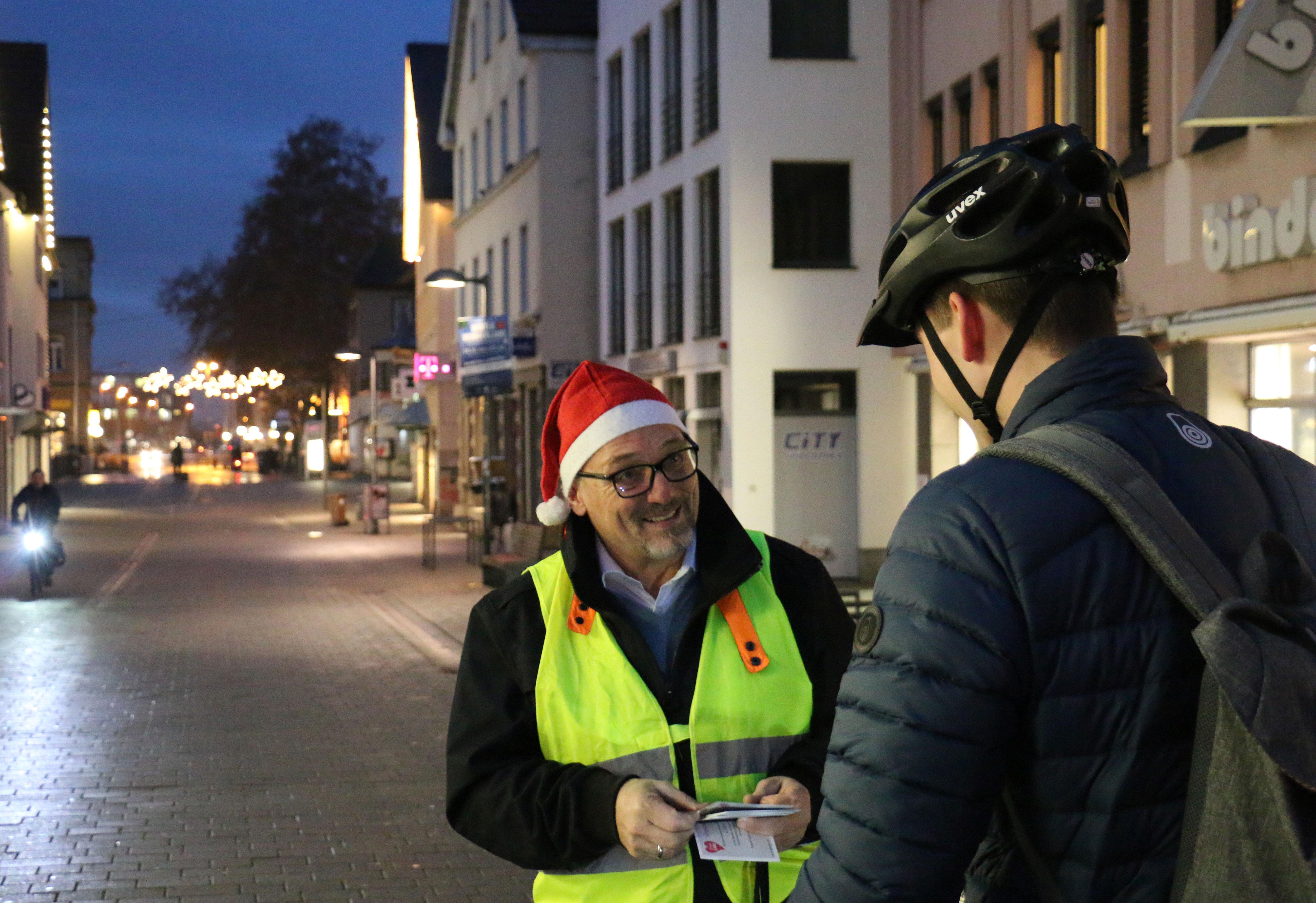 Erster Bürgermeister Günter Riemer übergibt bei der Nikolaus-Aktion einen Gutschein an einen Radfahrer.
