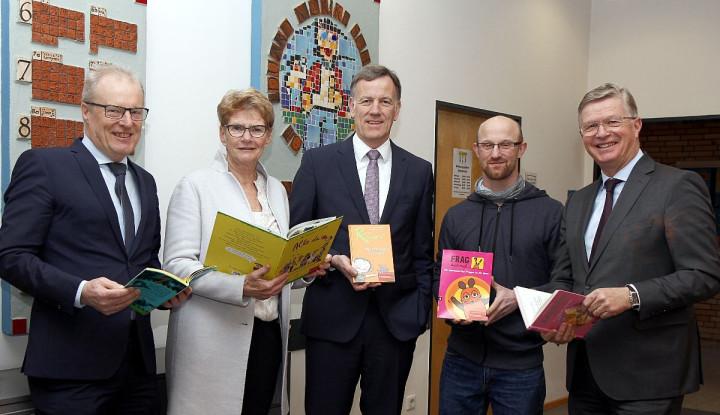 Oberbürgermeisterin Matt-Heidecker präsentiert gemeinsam mit Repräsentanten der Kreissparkasse Esslingen--Nürtingen und Lehrern der Teck-Grundschule Kinderbücher im Rahmen einer Buchspende-Aktion.