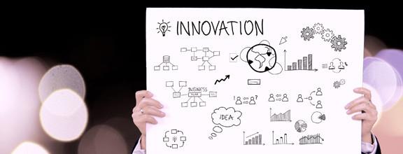 """Ein Schild mit der Beschreibung """"Innovation"""" wird hoch gehalten"""