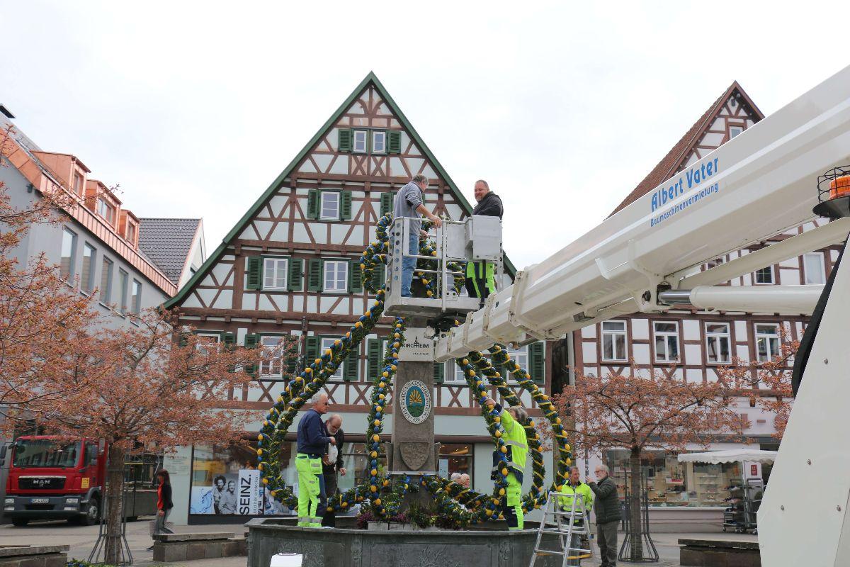 Der städtische Baubetrieb baut gemeinsam mit Mitgliedern des MSSGV des Osterbrunnen am Marktplatz auf.