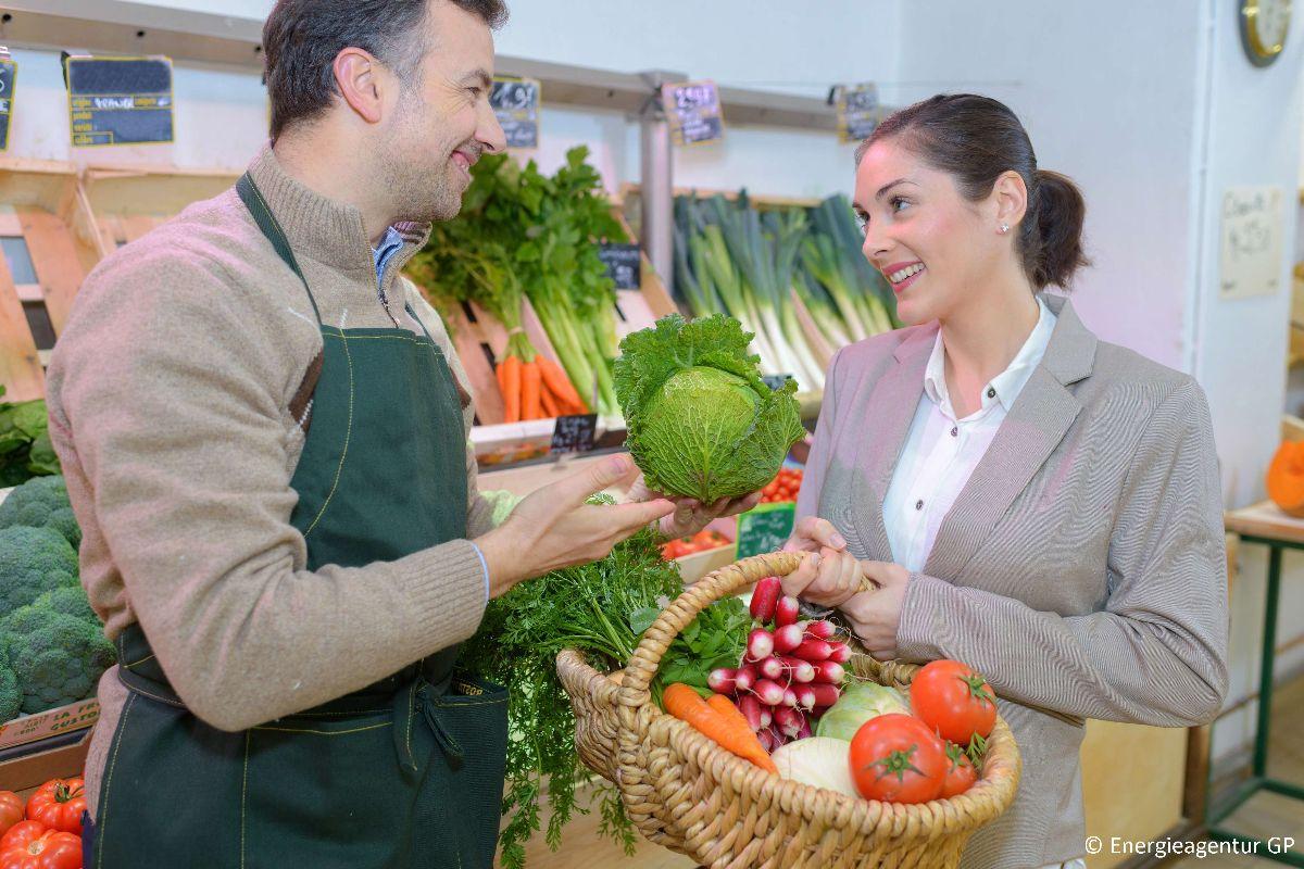 Ein Gemüsehändler übergibt einer Frau mit einem Korb voller Gemüse einen Kopfsalat.