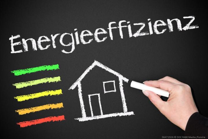 Eine Hand zeichnet mit Kreide ein Haus auf einer Tafel, Schriftzug Energieeffizienz