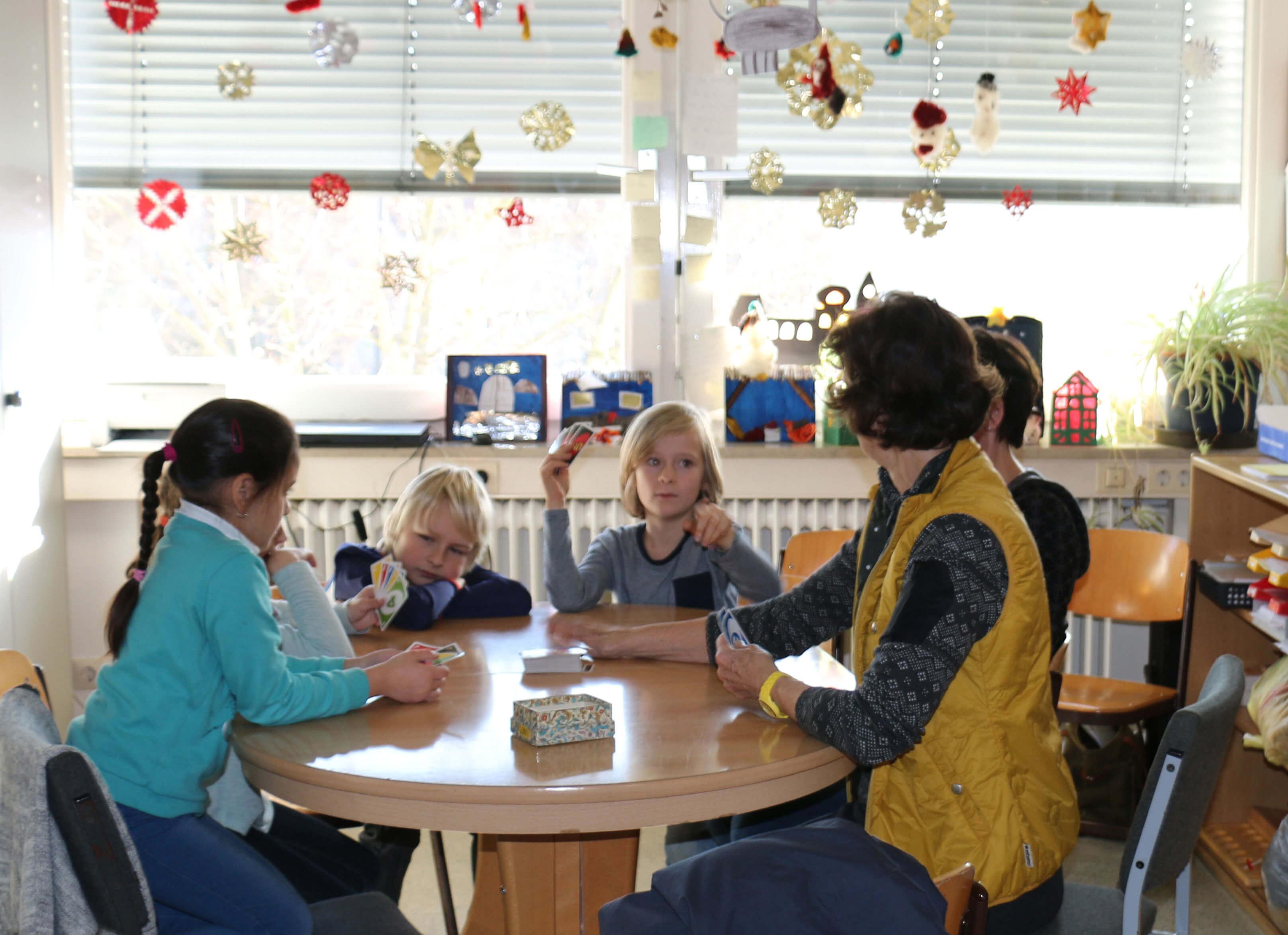 Kinder und Betreuerin beim Kartenspielen während der Kernzeitbetreuung