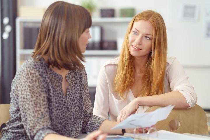 Geschäftsfrau erklärt einer Kollegin etwas