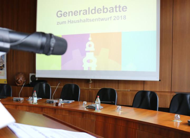 """Aufnahme vom Rednerpult im Sitzungssaal des Rathauses. Im Hintergrund ist eine Präsentation mit dem Titel """"Generaldebatte zum Haushalt 2018"""" zu sehen."""