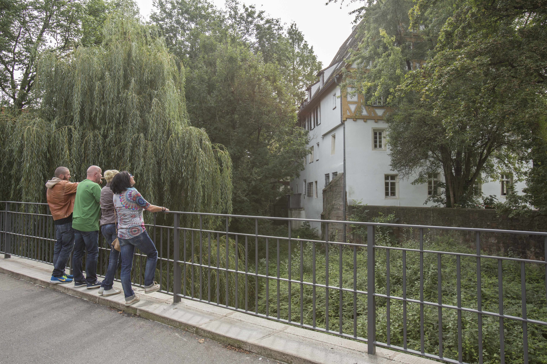 Vier Personen stehen auf einer Brücke und schauen in Richtung Flusslauf.