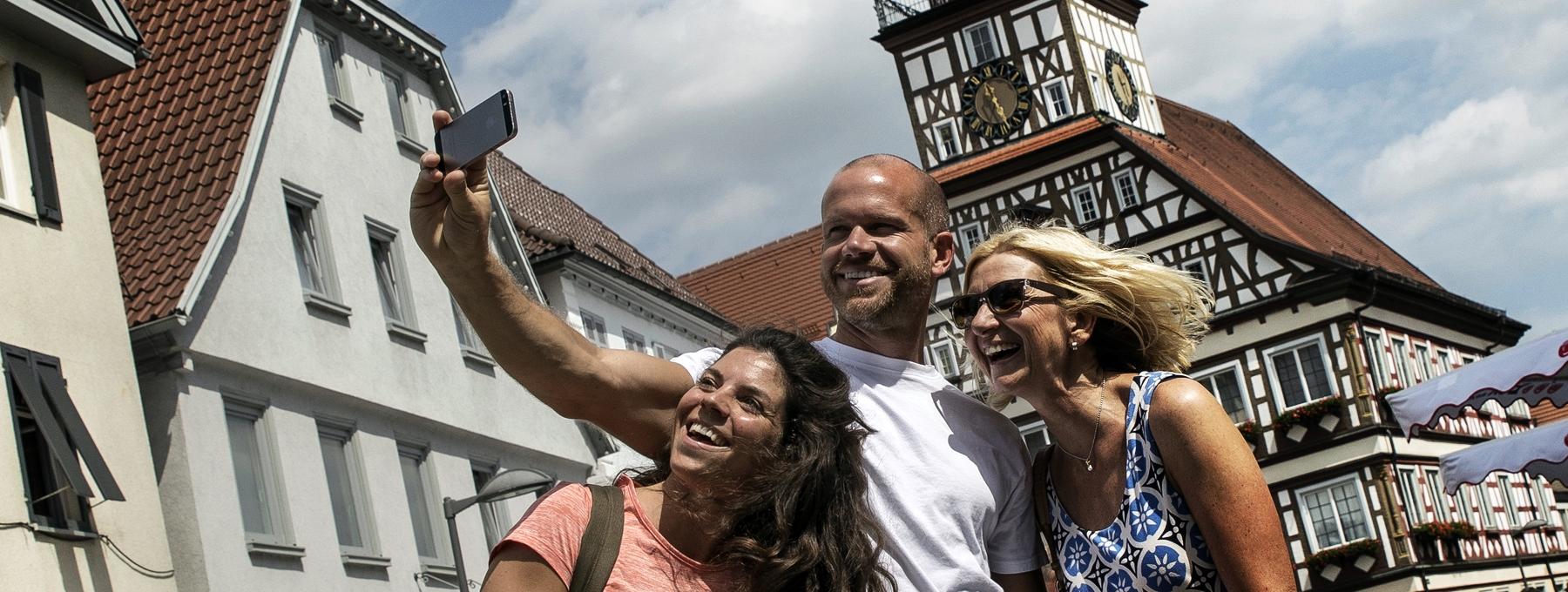 Drei Personen stehen mit einem Smartphone in der Hand vor dem Kirchheimer Fachwerk-Rathaus und nehmen ein Foto von sich auf.