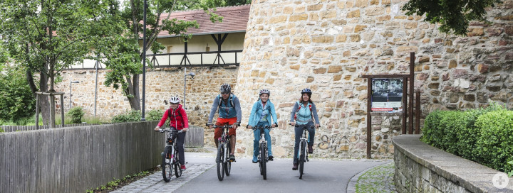 Blick auf vier nebeneinanderfahrende Radfahrer vor der Bastion
