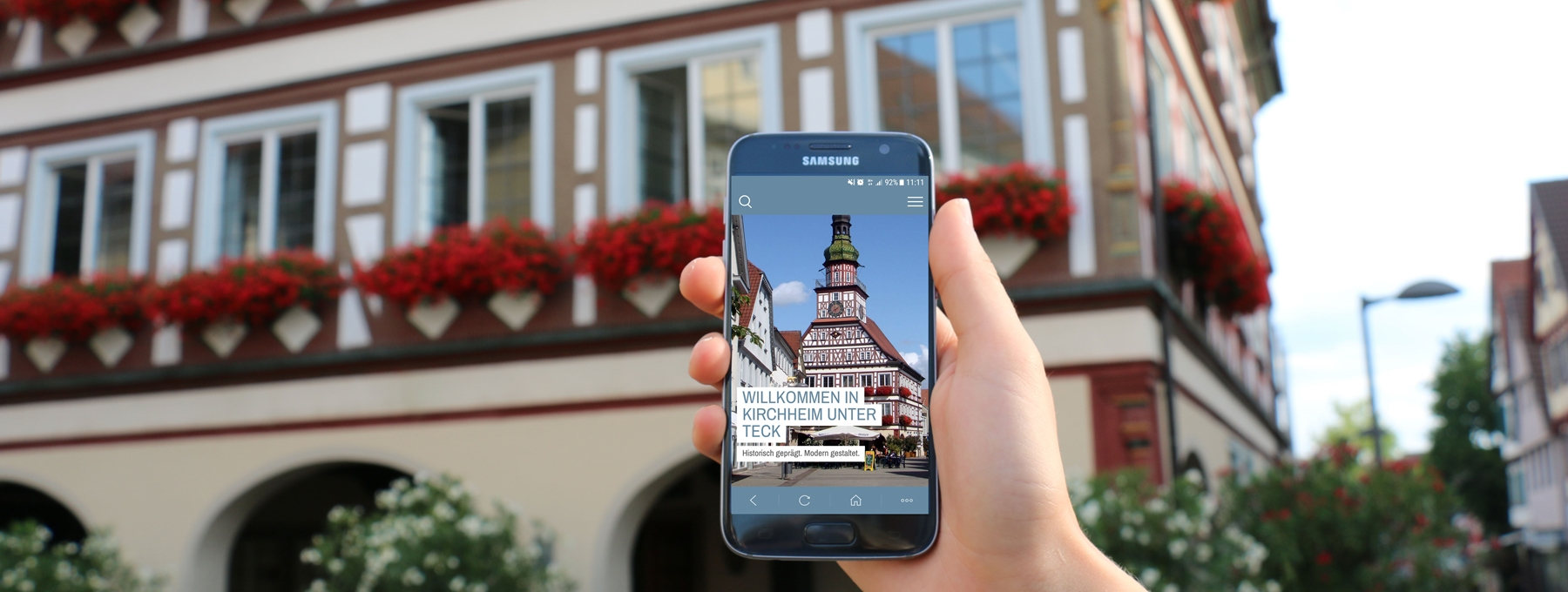 Ein Smartphone wird vor dem Rathaus in der Hand gehalten