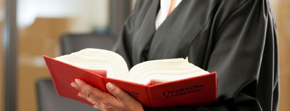 Anwältin mit aufgeschlagenem Gesetzbuch