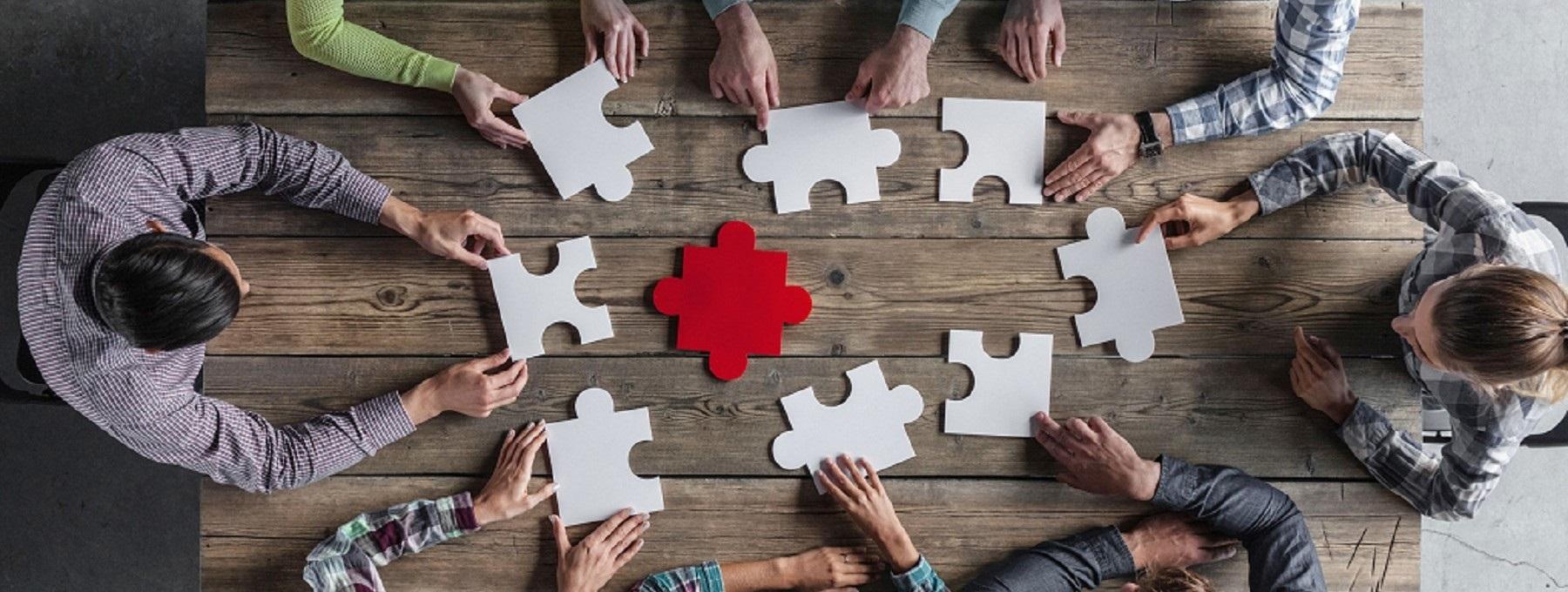 Mitarbeiter sitzen am Tisch und erstellen gemeinsam ein Puzzle