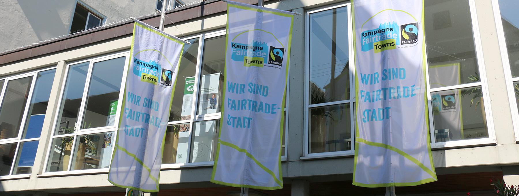 Fahnen der Kampagne Fair Trade Town am Seiteneingang des Rathauses