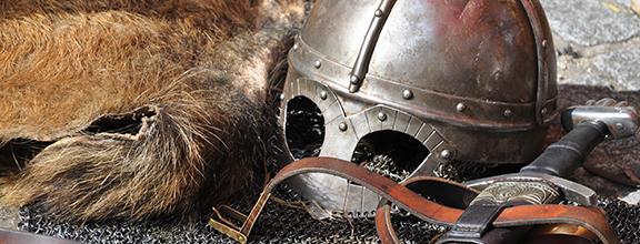 Historische Utensilien: Fell, Ritterhelm und Schwert