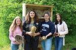 Vier Schülerinnen der Freihof-Realschule stehen vor dem halb gefüllten Insektenhotel. Jede von ihnen hat Baumaterial für das Hotel in den Händen.