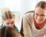 Junge Frau und Kinder bei der Hausaufgabenbetreuung