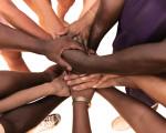 Hände verschiedener Hautfarben bilden ein Gemeinschaftsgefüge