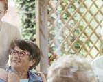 Junge Frau betreut Senioren, die im Garten Kaffee trinken