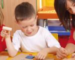 Erzieherin spielt mit drei Kindern an einem Tisch