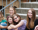 Schülerinnen sitzen auf einer Treppe