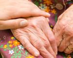 Frau legt ihre Hand auf die Hand einer älteren Frau