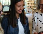Drei Frauen schauen auf einen E-Book-Reader in der Stadtbücherei