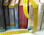 Mehrere Bücher stehen nebeneinander auf einem Tisch, auf ihnen liegt ein gelbes Maßband.