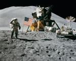Ein Astronaut steht mit vor seinem Mondfahtzeug und der amerikanoschen Flagge auf dem Mond.