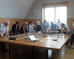 Mehrere Männer und Frauen begutachten Austellungsstücke auf einem Tisch im Jesinger Rathaus.