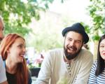 Junge Menschen sitzen lachend an einem Gartentisch.