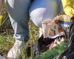Frau in Handschuhen sammelt Müll