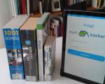 """Ein Tablet mit der Anwendung """"Freegal"""" auf einem Tisch, gemeinsam mit den Büchern """"1001 Songs, die sie hören sollten, bevor das Leben vorbei ist"""", dem """"Rocklexikon"""", sowie Büchern über """"Oper"""" und """"Jazz-Klassiker""""."""