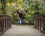 Ein blondes Mädchen mit Schulranzen läuft auf einem Weg