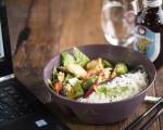 Ein Mehrwegbehälter der Firma reCIRCLE mit Esstäbchen, Curry, Reis und Salat neben einem Laptop und einem Getränk.