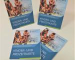 Vier Exemplare der neuen Kinder- und Freizeitkarte, hübsch angeordnet auf einem Tisch.