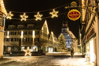 Blick auf das weihnachtlich beleuchtete Kirchheimer Rathaus und den Weihnachtsbaum vor dem Rathaus. Am linken Bildrand sieht man einen beleuchteten Stern am Marktplatz.