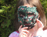 Ein Mädchen mit einer bunt geschmückten Maske.