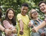 Fünf fröhliche, junge Menschen unterschiedlicher Herkunft zeigen einen Daumen nach oben.