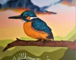 """Ein Graffiti-Bild von einem bunten Vogel auf einem Ast, darunter der Schriftzug """"Willkommen in Ötlingen"""", im Hintergrund eine Hügellandschaft."""