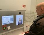 Ein Kunde steht vor einem Video-Reisezentrum der Deutschen Bahn