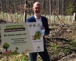 Oberbürgermeister Dr. Pascal Bader hält ein Schild mit Informationen zur Baumpflanzaktion im Talwald mit Hitradio antenne 1 hoch