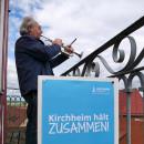 """Heribert Diemer von den Turmbläsern spielt auf dem Rathausturm Musik. Im Vordergrund ist ein Plakat mit der Aufschrift """"Kirchheim hält zusammen"""" zu sehen."""