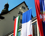 Blick auf den Seiteneingang des Rathauses, wo die ungarische, französische und serbische Flagge nebeneinander hängen.