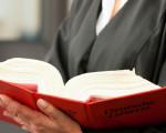 Anwältin mit aufgeschlagenem Gesetzbuch © Kzenon