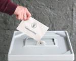 Wahlurne vor Schieferwand am Sitzungsaal und Person wirft ein Stimmzettel ein