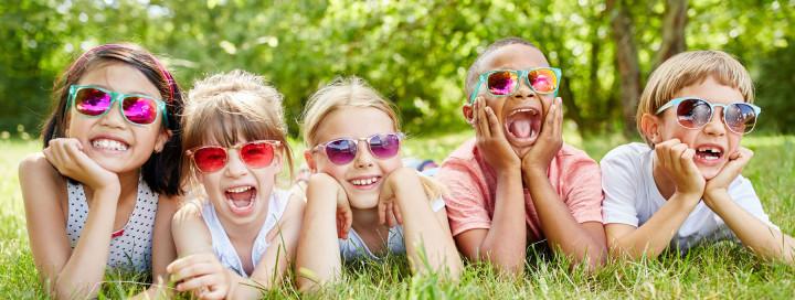 Fünf lachende Kinder mit Sonnenbrillen liegen auf grüner Wiese