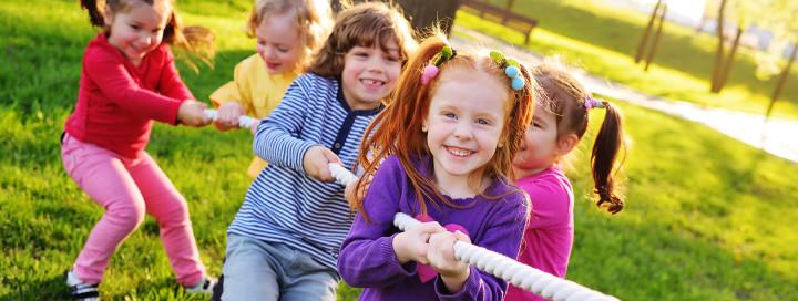 vier Kinder ziehen gemeinsam an einem Seil
