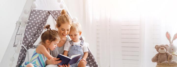 Eine junge Frau liest zwei Kindern etwas vor